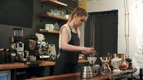 做手煮的咖啡,加grinded咖啡和倾吐热水的Barista 库存照片