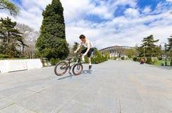 做把戏的年轻BMX自行车车手在室外的公园 免版税库存图片