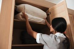 做投入的旅馆床枕头在碗柜 免版税库存图片