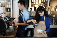 做拿铁或cappucino咖啡在咖啡的两亚洲barista 库存图片