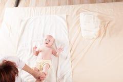 做按摩手和腿的小男孩小母亲 免版税库存照片