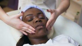 做按摩的年轻美容师在非洲妇女面孔 股票视频