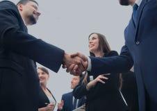 做握手的大小组不同种族的商人 免版税库存照片