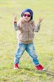 做摇滚n卷标志的逗人喜爱的小女孩 免版税图库摄影