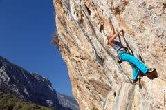 做攀岩训练的妇女在高伸出的岩石 库存图片