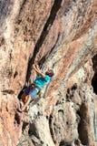 做攀岩训练的成熟人在高伸出的岩石 库存图片