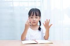 做数学的亚裔矮小的中国女孩通过计数手指 免版税库存照片