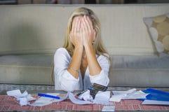 做文书工作和银行帐单认为的有吸引力的担心和绝望白肤金发的妇女计算的国内金钱费用 免版税库存照片
