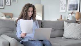 做文书工作的卷发妇女,当坐长沙发时