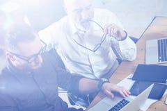 做新的企业方向的小组两个伙伴研究在现代办公室 工作年轻有胡子的商人  免版税库存图片