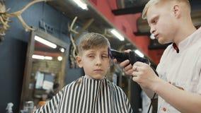 做新的理发的专业理发师在土坎和电动剃须刀帮助下 美丽的男孩和美发师或者 股票录像