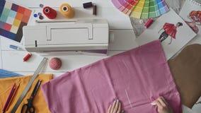 做新的衣裳的女性时装设计师追踪的织品样式 股票录像
