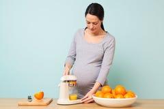 做新鲜的橙汁的孕妇。 免版税库存照片