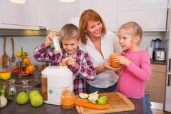 做新鲜的汁液的母亲、儿子和女儿在厨房里 免版税库存图片