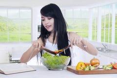 做新鲜的沙拉的妇女在厨房里 免版税库存照片