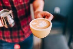 做新鲜的热奶咖啡和煮咖啡的咖啡店的专业侍酒者 免版税库存照片