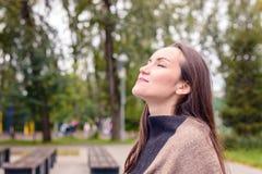 做新鲜的秋天空气的呼吸年轻美丽的妇女画象在一个绿色公园 纯净的大气空气的概念, envir 免版税库存图片