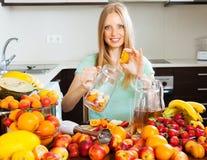 做新鲜的饮料的妇女由果子 免版税库存照片