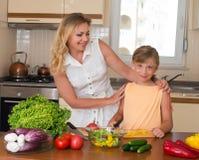 做新鲜蔬菜沙拉的少妇和女孩 健康家庭食物概念 一起烹调的母亲和的女儿,帮助孩子 图库摄影