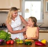 做新鲜蔬菜沙拉的少妇和女孩 健康家庭食物概念 一起烹调的母亲和的女儿,帮助孩子 库存照片