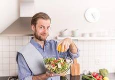 做新鲜蔬菜沙拉的愉快的微笑的人在厨房里 免版税库存图片