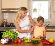 做新鲜蔬菜沙拉的母亲和女儿 健康家庭食物概念 一起烹调的母亲和的女儿,帮助孩子 免版税库存照片