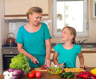 做新鲜蔬菜沙拉的母亲和女儿 健康家庭食物概念 一起烹调的母亲和的女儿,帮助孩子 免版税图库摄影