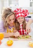 做新鲜水果快餐的妇女和小女孩 库存图片