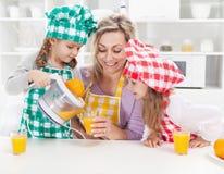 做新鲜水果汁的女孩和他们的母亲 库存照片