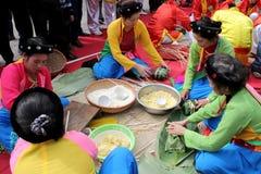 做方形的糯米的传统服装检查的人们 免版税库存照片