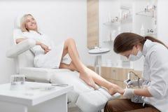 做方法微笑的客户脚的足病医生 免版税图库摄影