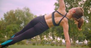做旁边板条锻炼的年轻逗人喜爱的运动的健身女孩特写镜头画象舒展她的胳膊在都市的公园 股票视频