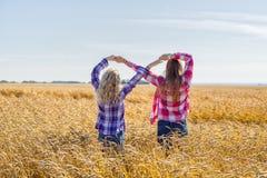 做无限标志的两个十几岁的女孩 免版税库存图片