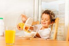 做早餐的小男孩倾吐的玉米片 库存图片