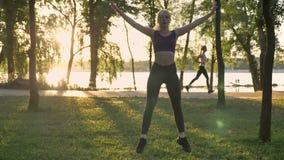 做星锻炼在公园,减重,健身式样跳跃,其他妇女的年轻俏丽的妇女跑后面,透镜 股票录像
