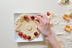 做曲奇饼的女性手由新鲜的面团 免版税库存图片