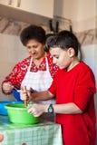 做曲奇饼的孙子和祖母 免版税图库摄影