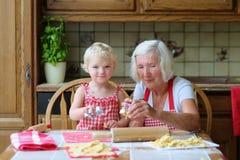 做曲奇饼的祖母与孙女一起 库存图片