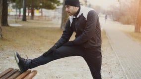 做有吸引力的人的赛跑者舒展为早晨锻炼做准备和跑步在冬天公园的锻炼 免版税库存照片