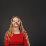 做有她的头发的凉快的年轻白肤金发的白种人妇女髭 免版税库存照片