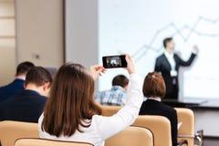 做有手机的女实业家录影在业务会议 库存照片