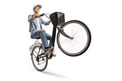 做有自行车的少年一个自行车前轮离地平衡特技 库存图片