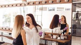 做服务的美容师对沙龙的少妇 免版税库存图片