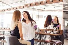做服务的美容师对沙龙的少妇 库存照片