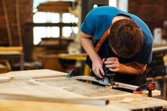 做木家具的木匠在商店 库存图片