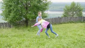 做杂技车轮的青少年的女孩在一起走在自然的草坪 影视素材