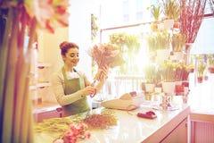 做束的微笑的卖花人妇女在花店 免版税库存图片