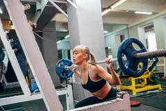 做杠铃的健身妇女在健身房蹲 免版税库存照片