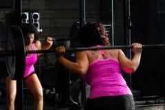 做杠铃蹲坐的女性举重运动员 图库摄影