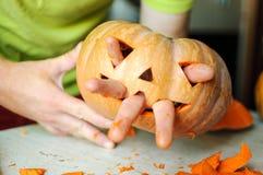 做杰克o灯笼的过程 万圣夜南瓜与男性手指的妖怪面孔的滑稽的图片 库存照片